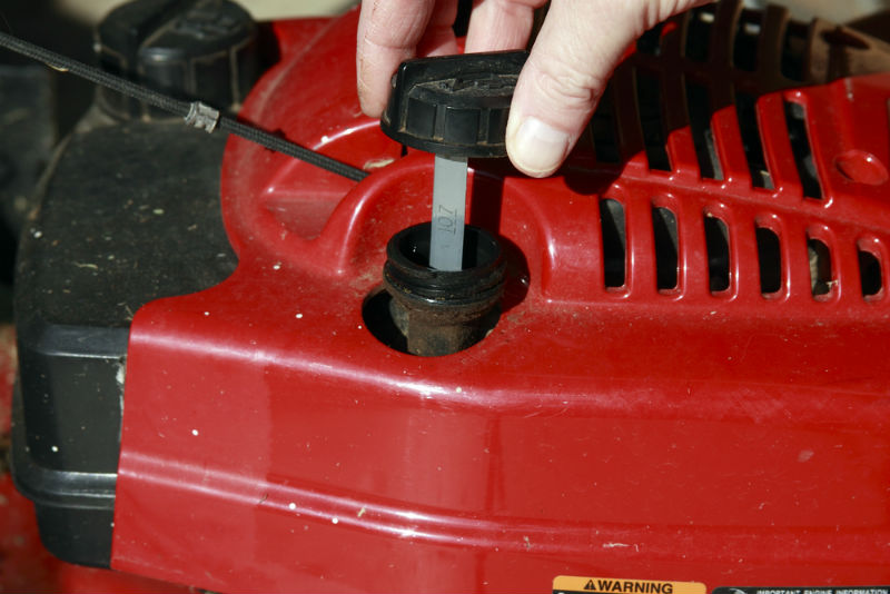 Checking the oil in lawn mower